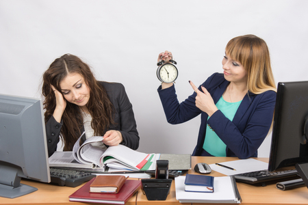 slacker: Two girls in the office awaiting the end of the day and look at the clock