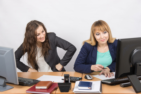 deceptive: Office worker with feigned indignation looking at the colleague sitting next to the computer innocently
