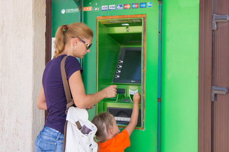 withdraw: Anapa, Russia - September 20, 2015: A young girl with the child to withdraw money from the ATM Sberbank