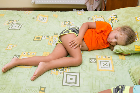 frazzled: Little girl is sleeping on his side on the big bed without a blanket Stock Photo