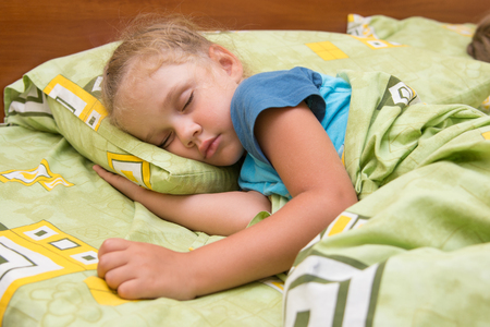 frazzled: Little girl sleeping on her side in bed with his hand under the pillow and covered with a blanket Stock Photo