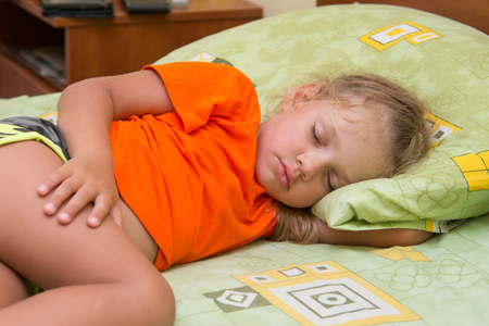 frazzled: Little girl sleeps on his side in his hand under the pillow of the bed Stock Photo