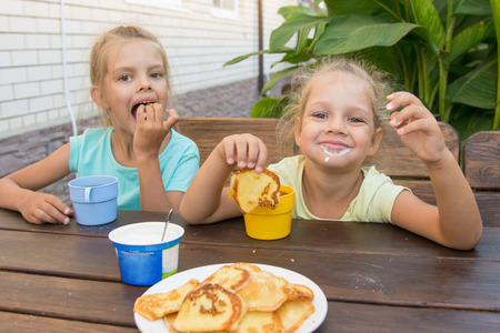 soiled: Satisfied children at a table in the courtyard eating pancakes with sour cream