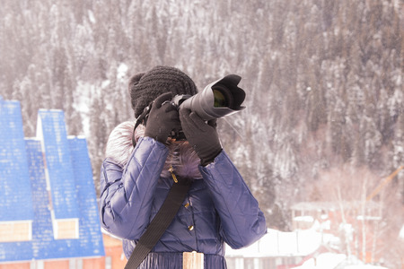 telephoto: A young girl takes pictures winter mountain landscape in a snow storm on a SLR camera with telephoto lens