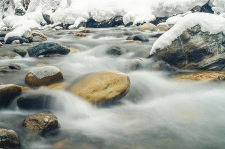 rapidly: Rapidly flowing mountain river, blurred by a slow shutter speed Stock Photo