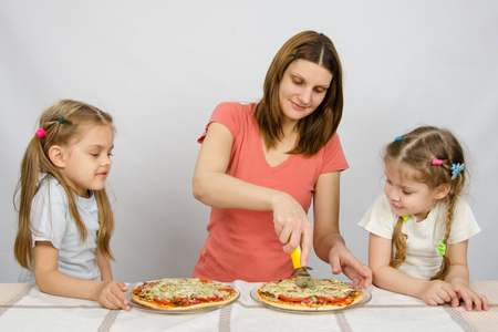 eagerly: Mom cuts the pizza, and the two little girls eagerly look