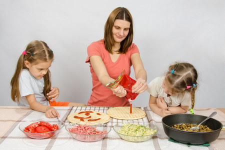 enthusiastically: Two little girls enthusiastically watched as mum pours ketchup basis for pizza