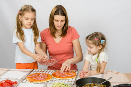 eldest: The eldest daughter helps her mother cook a pizza, and the youngest is watching them