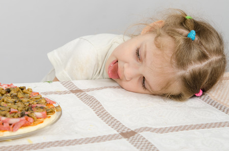 rested: Little girl with protruding tongue rested her head on the table and looks at the pizza