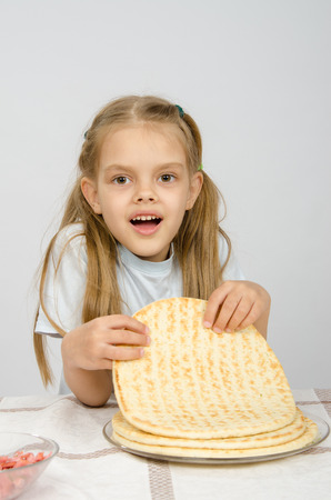 slight: The girl with a slight smile holding a pizza crust on a plate Stock Photo