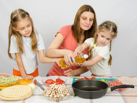 enthusiasm: Two little girls at the kitchen table with enthusiasm to help my mother to pour vegetable oil in a frying pan Stock Photo