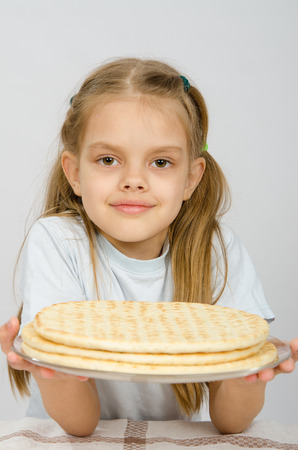 pizza crust: The girl with a slight smile holding a pizza crust on a plate Stock Photo