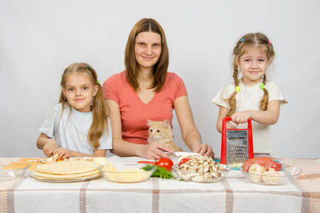 they are watching: Mother and two little girls at a table prepared ingredients for the pizza. They were watching a cat Stock Photo