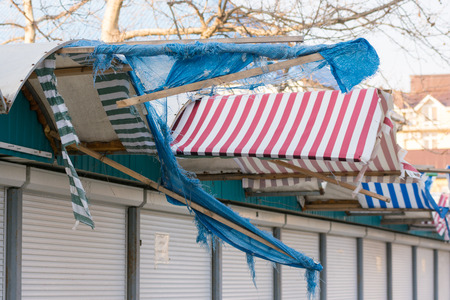 awnings: Torn fabric awnings over the closed seaside shops in the offseason