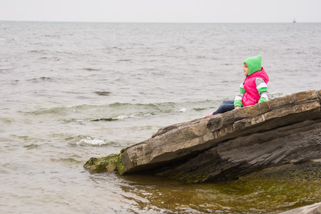7 year old girl: Warmly dressed little girl sitting on a piece of coastal cliffs and looking at the sea Stock Photo