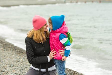 rubbing noses: Little girl and her mother touching noses on the beach in cold weather Stock Photo