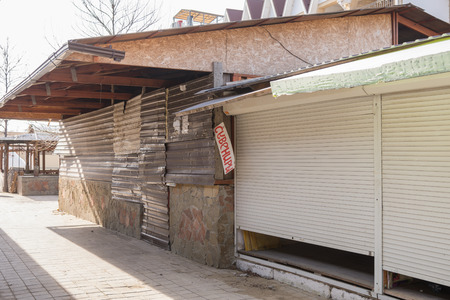 boarded: Closed trade pavilions and boarded metallosayding building a sidewalk cafe on a deserted seaside street Stock Photo