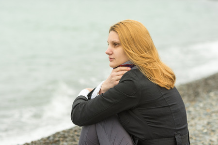 beach wrap: A girl sits on a pebble beach by the sea on a cloudy day in cold weather, covering the neck scarf