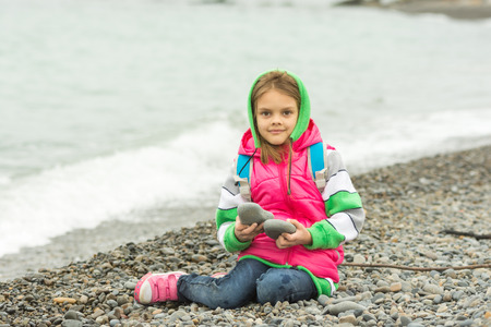 7 year old girl: Seven-year girl sitting on a pebble beach in the warm clothes and looks in the frame