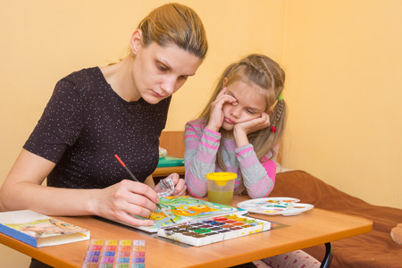 7 year old girl: Artist teacher shows how to paint watercolors, and the child rubs his eyes wearily