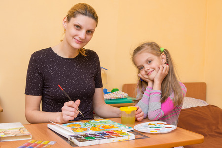 7 year old girl: a drawing teacher teaches a little girl paint watercolors