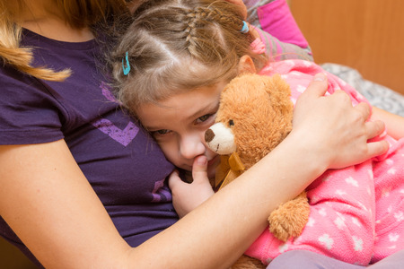 solace: Little girl with a teddy bear clung to her mother with a sad expression on his face Stock Photo
