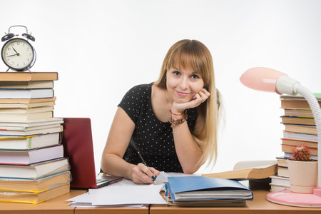 Ella se dedica a la mesa atestada de libros en la biblioteca con una sonrisa se ve en la trama