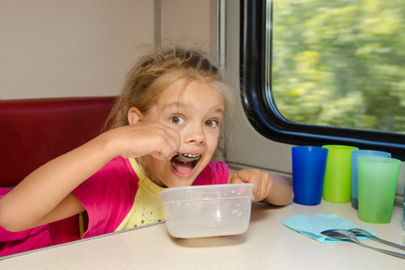 tedious: The girl on the train sits at a table on the lower place in the second-class compartment of the car and eats it with relish spoon