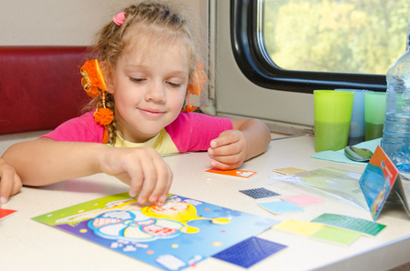 tedious: A small child in a train of fun playing at the table at the lower place in the second-class compartment wagon