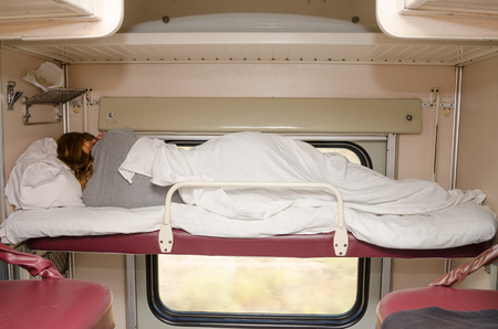 turn away: Passenger train sleeping on the top shelf of the side seats in the second-class carriage turned to the wall