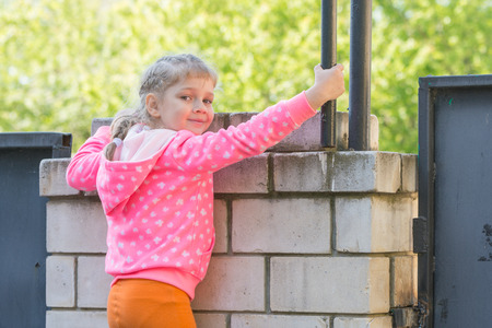 look pleased: Five-year girl climbed on a brick fence and turned around looked at the frame