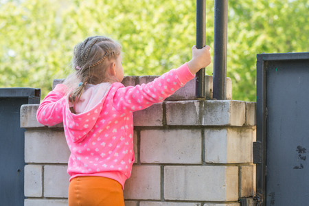 climbed: Five-year girl climbed on a brick fence and looks for him