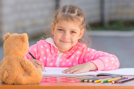 Girl draws with crayons and smile, he looked into the frame