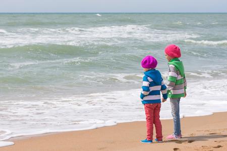 mujer mirando el horizonte: Dos niñas la mano de pie en la playa y que mira en la distancia