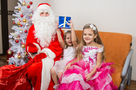 cherished: Santa Claus presented the first gift girls Stock Photo