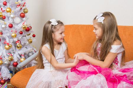 manos unidas: Dos chicas hermosas en vestidos de espera regalo unieron sus manos