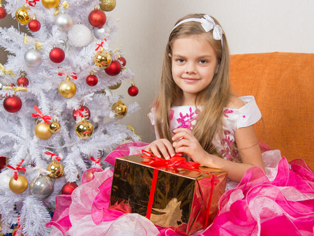 cherished: Seven-year girl in a beautiful dress sits with a gift in their hands