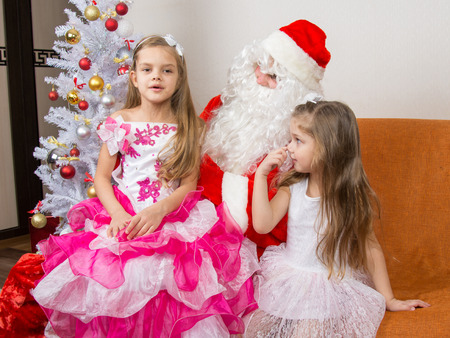poem: The older girl is sitting on the lap of Santa Claus and tells poem