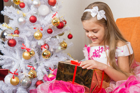 considering: Seven-year girl in a beautiful dress is considering a gift sitting on the couch at Christmas tree Stock Photo