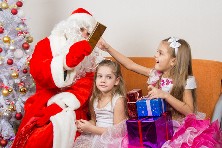 cherished: Santa Claus gives gifts to one girl, the other sitting in the waiting