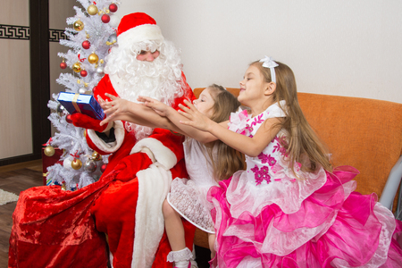 'grandfather frost': Two girls are drawn for a gift that took Grandfather Frost Stock Photo