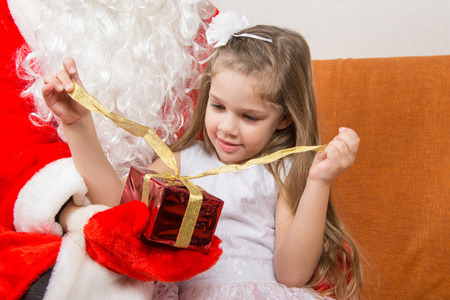 baby open present: Girl unleashes a red ribbon gift in the hands of Santa Claus