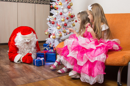 puts: Two girls saw that Santa Claus puts presents under the Christmas tree Stock Photo