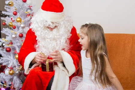 cherished: The girl with interest looks like Father Christmas helps to open her gift