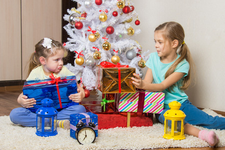 dismantle: Two girls share presented New Year gifts at the Christmas tree
