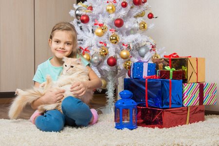 seven year old: Joyful seven year old girl with a cat sitting under the Christmas tree with gifts Stock Photo
