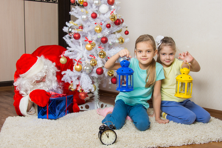 cherished: Two girls with flashlights waiting for Santa Claus at the Christmas tree in New Years Eve Stock Photo