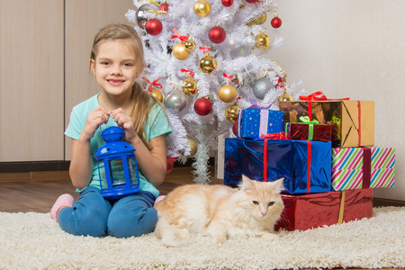 inseparable: Seven-year girl sits with a cat under the Christmas tree with gifts and smiling happily