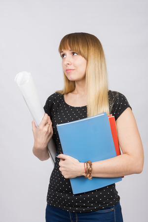 sadly: Young girl student with folders and a roll of paper in his hand sadly looks aside Stock Photo