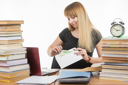 reluctance: The girl puts money in an envelope to bribe the teacher in the exam Stock Photo